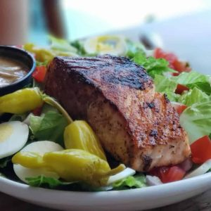 Grilled salmon and salad on a white plate.