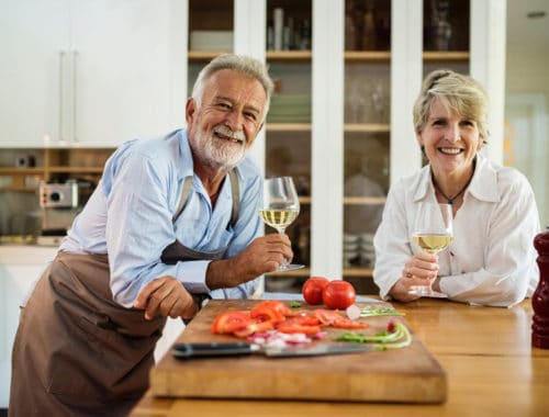 Couple standing in kitchen drinking white wine
