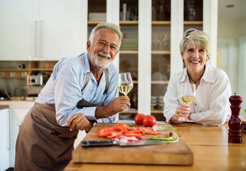 Couple standing in kitchen drinking white wine