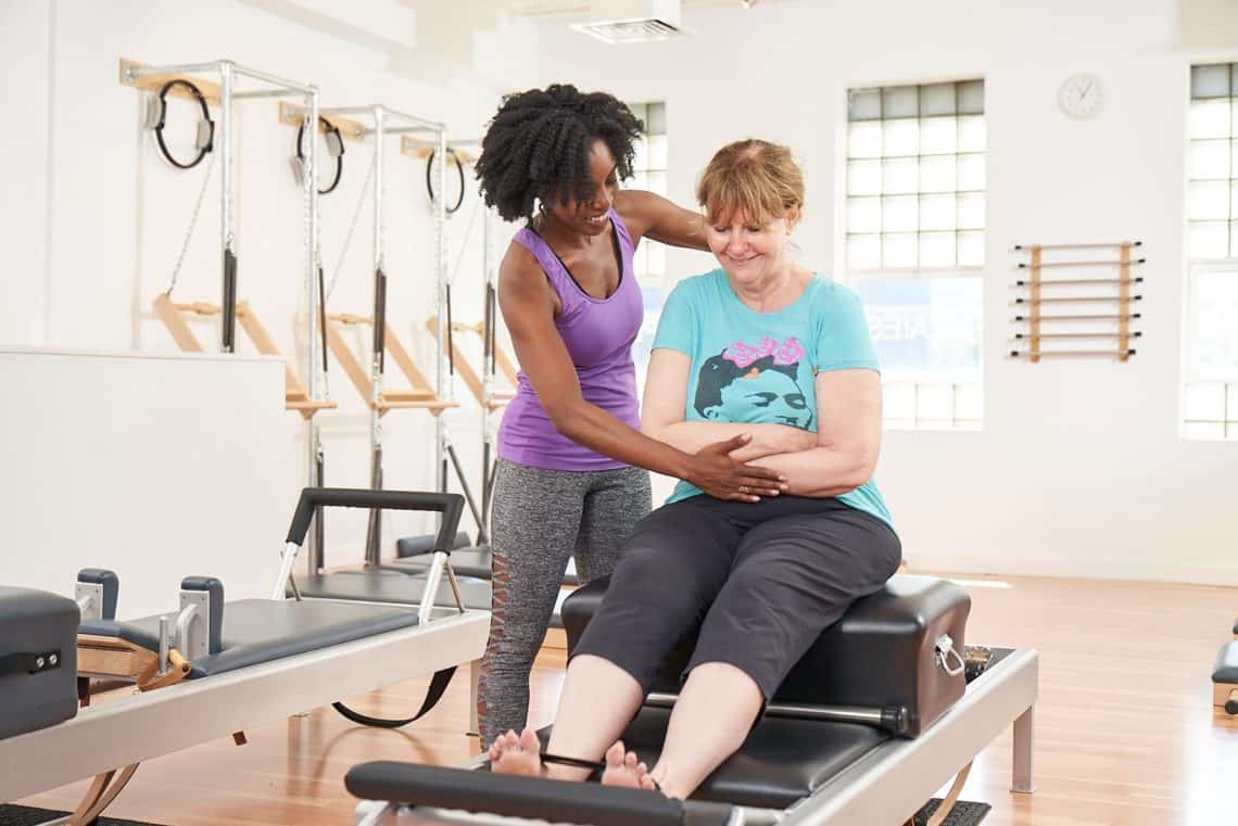 Woman starting Pilates with trainer by her side.