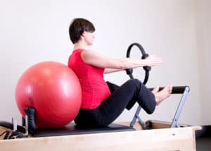 Pregnant woman doing Pilates for health and wellness.